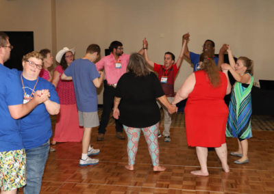 A group of conference-goers hold hand with another to form a circle as they dance together.