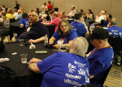 SOAR conference attendees visit with one another while sitting around a table.