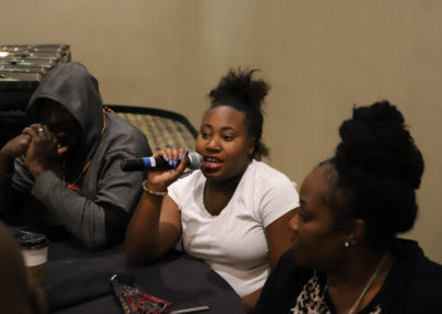 Participant asks a question into the microphone as she is attends Ollie Cantos's session at the 2019 SOAR Conference.