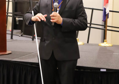 Ollie Cantos stands holding a microphone as he gives his presentation at the 2019 SOAR Conference.