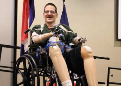 Travis Schaffer, self-advocate from Nebraska, is pictured seated on stage while presenting to the SOAR conference crowd.