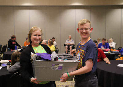 Two raffle winners pose with a metal tub of prizes that they have just won.