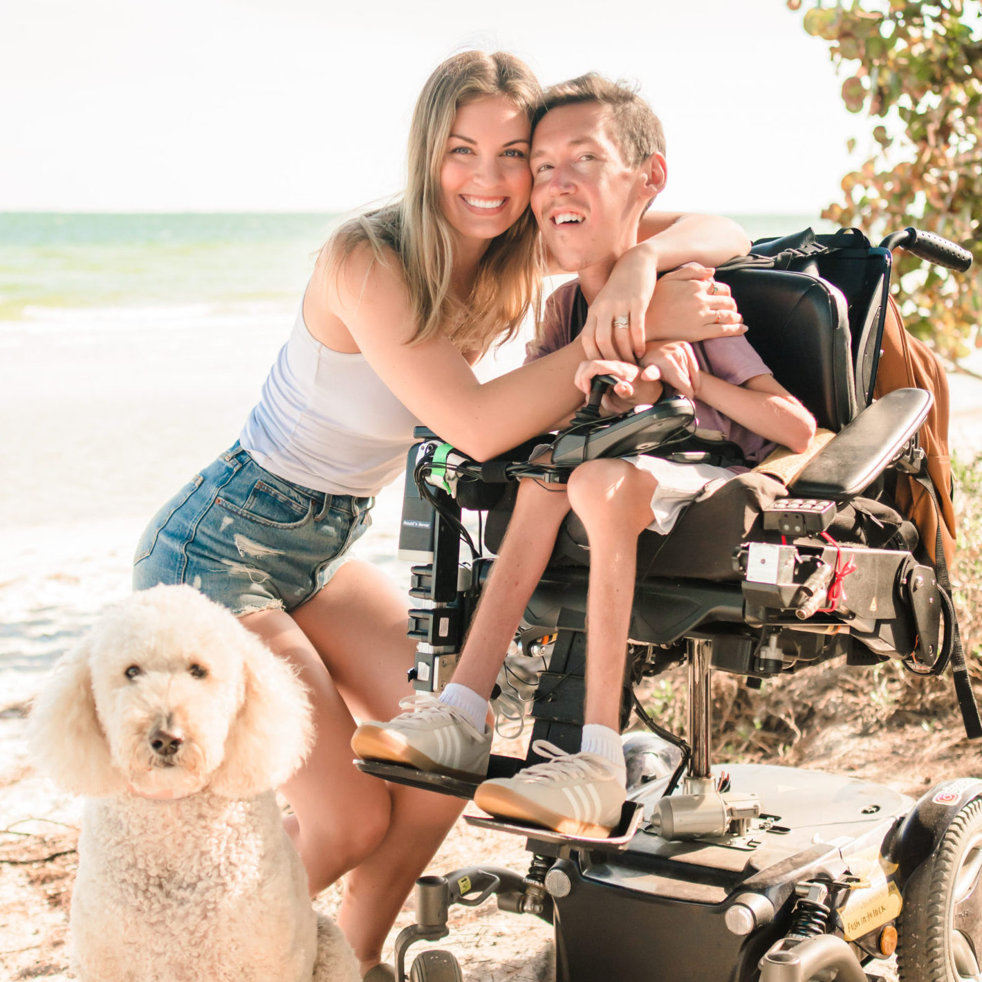 Photo of Hannah, Shane, and their Goldendoodle on the beach.