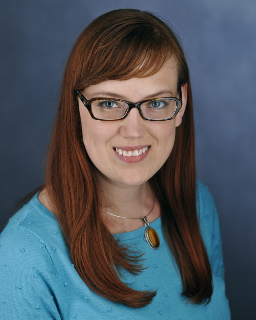 Photo of Carrie Wendell-Hummell. She is sitting in front of a blue background and smiling.