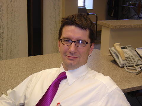 Photo of Brad Muerrens. He is sitting in frnt of a desk and smiling.