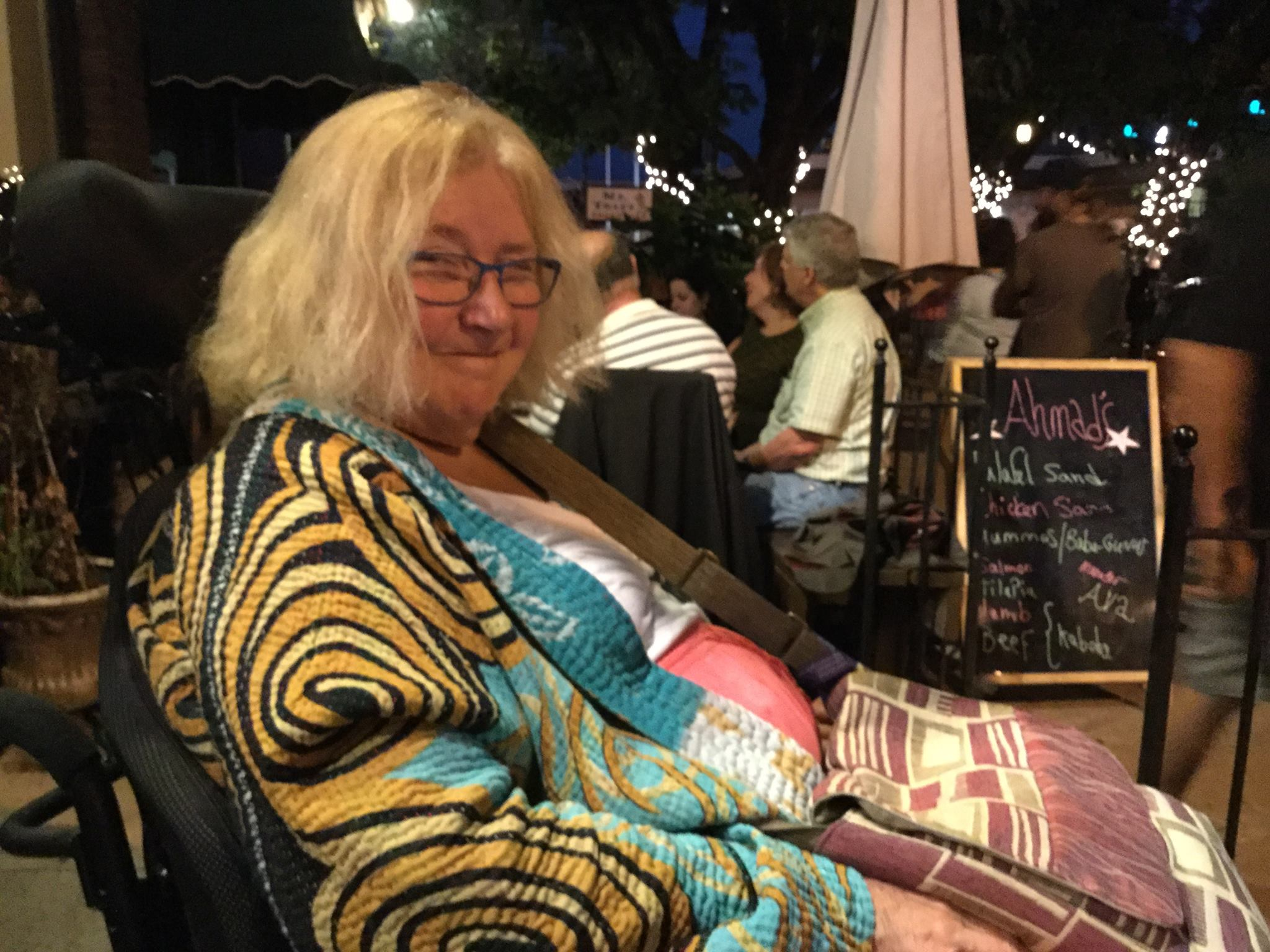 Photo of Kathy Hoell. She is sitting in a restaurant and smiling.