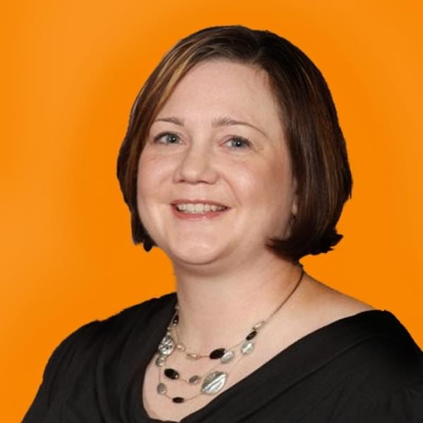 Photo of Jenn Wolff. She is sitting in front of an orange background and smiling.