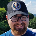 Photo of Brady Werger in front of trees. He is wearing a baseball cap and smiling.