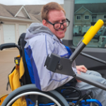 Photo of Michael Martin sitting in a wheelchair. He is looking over his right shoulder and smiling.