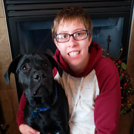 Photo of Julie Mueller with her dog. They are both sitting in a chair together.